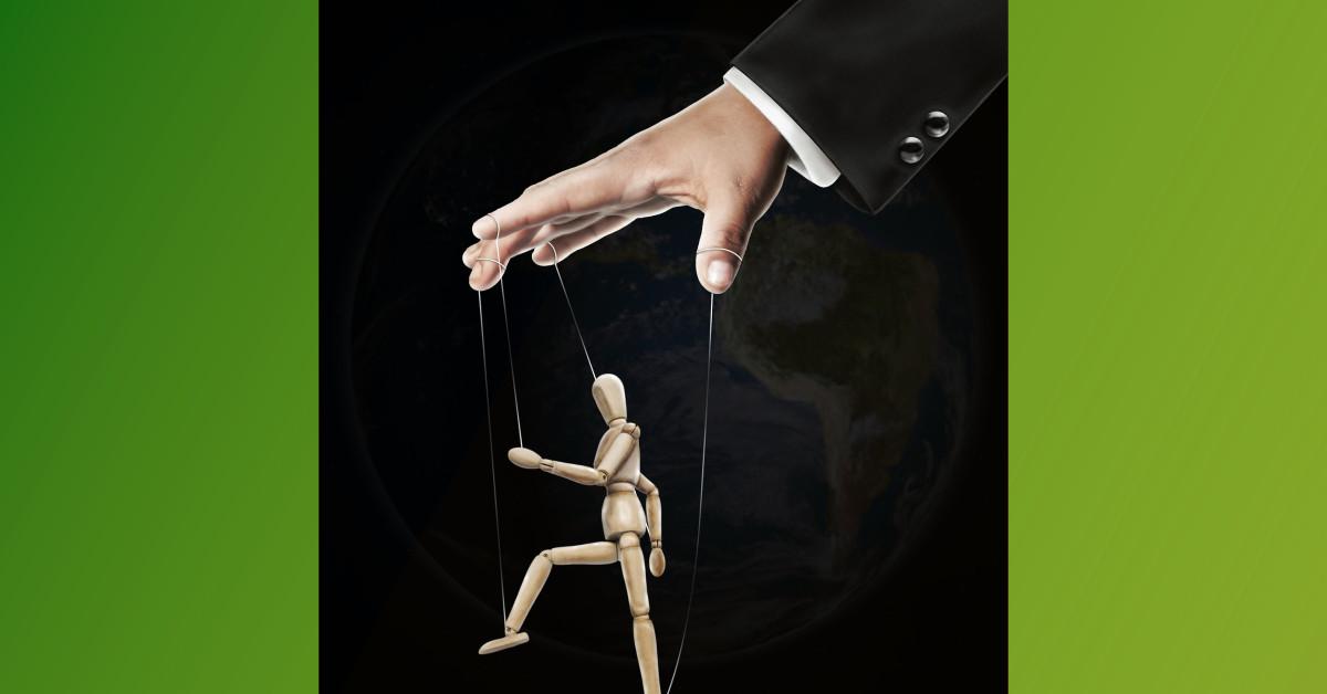 Man's hand pulling marionette strings